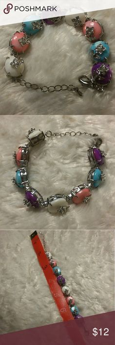 Multi-colored Silver Tone Bracelet Elegant bracelet with multi-colored stones and a decorative flower with a rhinestone on each  Pretty pink, blue, purple and white stones Some of the silver tone is starting to rub off on the back side of the bracelet and clasp which cannot be seen when worn- see pictures  Roughly 7 1/2 inches long  Lobster clasp closure Pet-free, pest-free, non-smoking home Jewelry Bracelets