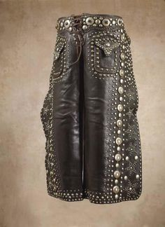 These stunning chaps in the style popularized by the  legendary cowboy actor, Tex Cooper (1876-1951)  are adorned with thousands of brass and nickel studs  in vertical, round and star patterns, 26-slotted conchos,  2 exterior pockets, c 1915 Established a world record   chap price 14 years ago when they sold at High Noon's   1994 Mesa, Arizona, auction for $11,000 Property from  the collection of R. Michael Kammerer, Jr., Santa Fe, NM