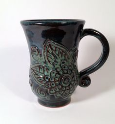 This mug was made on a pottery wheel, I added a handle, and then I slipped trailed a henna inspired botanical pattern. It is made of a