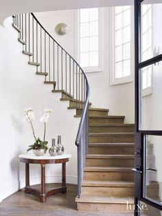 Transitional White Staircase with Reclaimed-Oak Plank FlooringSleek new balusters and an iron railing modernize the entry's winding staircase. A table from Joyce Horn Antiques rests on reclaimed-oak plank floors from Custom Floors Unlimited. Exterior Stair Railing, Iron Stair Railing, Staircase Railings, Bannister, Stair Treads, White Staircase, Curved Staircase, Staircase Design, Winding Staircase