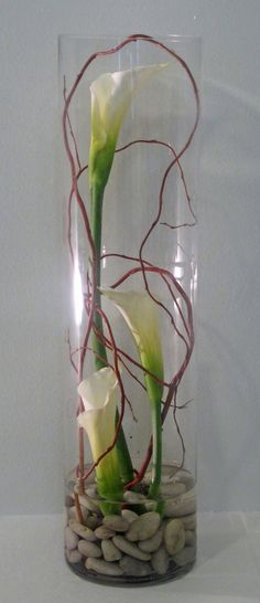 Long cylinder vase, pebbles, water, calla lillies and coloured vine or reeds creates a beautiful Asian inspired arrangement.