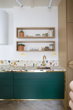 a colorful terrazzo kitchen countertop and emerald and gold cabinets look stylish and chic