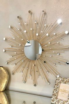 Art Deco sunburst mirror surrounded by wooden rods, with mini mirrors and diamond gems perfectly placed throughout.