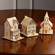 £16.99 Set of 3 Wooden Buildings  Create a 19th-century winter village scene with our laser-cut wooden buildings, inspired by traditional German designs. The Church, Hostelry and House have LED lights to give a cosy glow.
