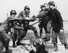 US troops of the 69th Infantry Division (left), shake hands with Russian troops…