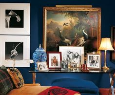 "An image from Ralph Lauren's home in Bedford, CT… I love how he mixed modern with traditional art, furniture and fabrics to create a mesmerizing space. The deep ""champion"" blue walls with the blue & white vase set the color pattern. Tartan plaids and traditional red horse blankets finish the look and pull out the color in the peacock oil painting."