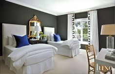 The guest room is a trademark of Ashley Goforth's – black walls, white linens, contemporary lines mixed with gilt antiques.