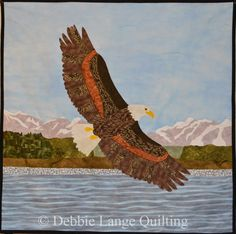 """Soaring Eagle Quilted Wallhanging.Finished size 32"""" by 32"""". An original designed by Debbie Lange and Eric Lange.  The blue sky and water was hand dyed. The background landscape was inspired by a photo taken on an Alaskan cruise. I can make a custom Keepsake Quilt for you. email to:DebbieLangeQuilting@gmail.com www.DebbieLangeQuilting.blogspot.com.  Facebook:DebbieLangeQuilting. Pinterest:DebbieLangeQuilting"""