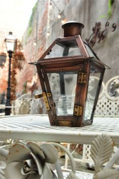 """Commemorate time spent in #NewOrleans with a French Quarter 9"""" Tabletop Lantern from Bevolo. Each handcrafted lantern is available in gold, nickel, and antique copper.  Indoors or out, the charm and ambiance from the glow of this lantern brings you back in time to courtyards of the old Vieux Carré. #Bevolo #FrenchQuarter #lanterns"""