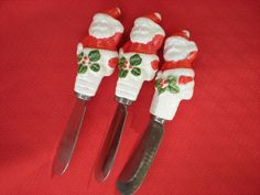 Santa Spreaders, set of 3 (identical). Porcelain? Santas have three colors: red, white and green.  Red coat/hat, white face pants, large green holly pattern beneath coat. Left arm raised high as in waving.