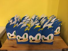 Sonic the Hedgehog treat bags. Cut store bought gift sack to create his quills. Cut eyes from white construction paper and add green ovals for eyes. Cut a long shoe shape from manilla paper for face and black tear-like shape for nose. Assemble, glue, and add details with black marker.