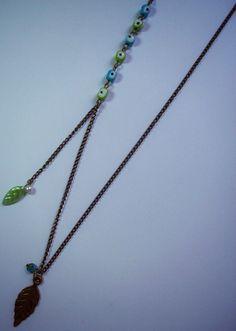 Collar Hojitas de invierno  Materiales: Cadena y dije pavonados, cuentas de vidrio, perlas y dije de plástico  Valor: 15.000