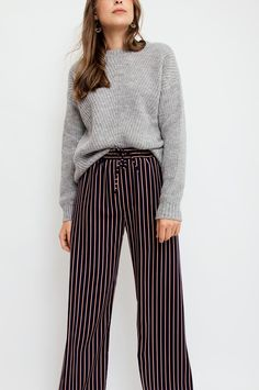 These navy trousers feature vertical stripes in burgundy, ocher, ecru and are finished with side pockets and an elasticated waistband. Style with a sweatshirt for a laid-back look or opt for a ruffled blouse for dressier occasions. From Sienna With Love. Available at Sienna & Faye.
