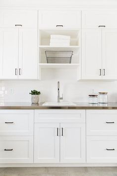 All white laundry room features white shaker cabinets for White kitchen cabinets with oil rubbed bronze hardware