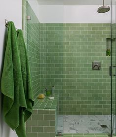 Gorgeous green and white themed bathroom features polished nickel towel hooks holding green bath towels beside a seamless glass shower fitted with green subway wall tiles surrounding tiled niche, a green tiled bench, and white marble grid floor tiles fixed beneath a rain shower head.