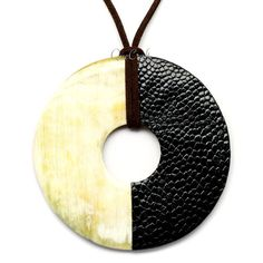 A beautiful pendant handmade from buffalo horn and ostrich leather. High polish finish. Lightweight. Actual colors may vary. 3.15 (8cm) diameter.