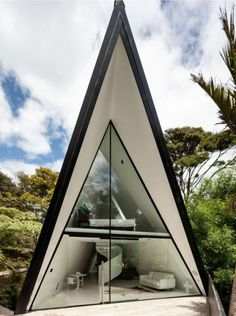 Tent House by Chris TateA glass-clad gable opens up like tent flaps, giving a direct view to the compact, black and white interior.