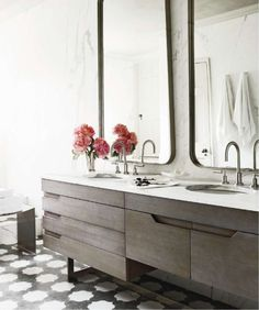 Calacutta marble wall,Contemporary in style, driftwood toned cabinets, large mirrors,  black & white tile floors
