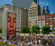 Crown Fountain, Chicago, southwest corner of Millenium Park. Glass towers stand at each end of a shallow reflecting pool. Faces of 1,000 Chicago residents are displayed onto LED screens - looks like they are spitting water.