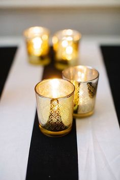 Gold glass candle holders on a striped table cloth #wedding #tablescape #centerpiece #gold #goldblack