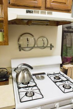 15_Storage_And_Organization_Ideas_For_Your_Kitchen_-_Use_a_towel_bar_to_store_pot_lids[1]