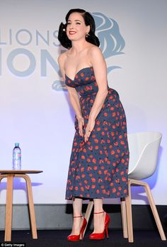 Glamorous: The burlesque dancer flaunted her flawless decolletage as she slipped her famou...