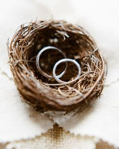 Wedding bands rest in a tiny bird's nest affixed to a linen ring pillow