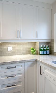 Gray Glass Tiles - Contemporary - kitchen - Emily Hollis Interior Design-L shaped kitchen features white cabinets paired with speckled countertops and gray glass mini-subway tile backsplash.