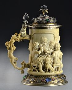 """A Fine German or Austrian Carved Ivory Tankard -  The body finely carved in high relief to depict children in various scenes drinking wine, having a carved dog, urn, beef and fish on a platter on draped tables, having a jeweled inset silver top and base with a gold wash, additional carved children in the round as handle, with beast form thumb rest and jeweled inset flora formed finial, unmarked, probably German or Austrian, measures 7.75""""H, circa 19th century."""