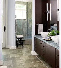 Tumbled-limestone tiles in cool gray-blue hues pave this bathroom floor and set the tone for a masculine look and feel. The cherry cabinets balance the tile flooring and bring out the varying texture and color of the tiles.