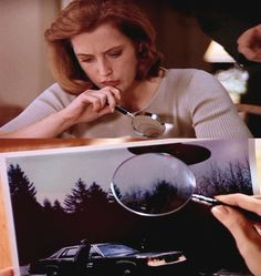 Scully uses a magnifying glass to inspect a possible fraudulent UFO photograph