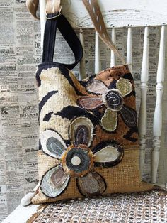 This CROSSBODY HOBO BAG is done in warm earth tones with just a touch of animal instinct! The two scrappy flower designs hand-stitched to the