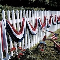 Nobody at this house is on the fence about patriotism! Red, white, and blue bunting draped loosely on a picket fence is a stunning striped visual for your yard.