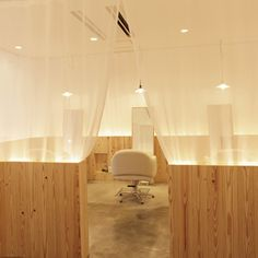 Japanese architects Maker completed a hair salon featuring gauze partitions and booths in untreated wood.