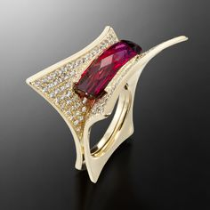 A modern ring design by Adam Neeley. Enchante Tourmaline Ring is charming and lively. In this unique ring design, a vivid rubellite tourmaline is set delicately between petals of yellow gold, covered in luxurious diamond pavé.