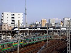 Keisei Sky Liner heads to Narita Air Port in front of Tokyo Sky Tree over a commuting train.