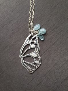 "Handcrafted in fine silver (.999%), this butterfly pendant is complimented with three dainty aquamarine gemstones. It hangs at 30.25"" on sterling silver chains of two style. A one-of-a-kind pendant ideal for the butterfly lovers! Great for layering or worn alone! ($75) #butterflyjewelry #modernjewelry #silverjewelry"
