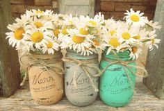 I think Mason jars would be great -- we can paint them or not. But they have that rustic feel that works with the ballroom. We can put inexpensive flowers in them like daisies or baby's breath.