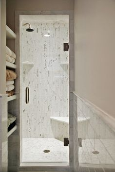 This marble shower uses a sleek corner seat to provide a more relaxing space - even though the shower is smaller.