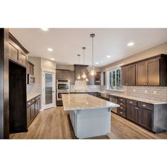 Whats not to love about the spacious kitchen. Espresso Shaker cabinets and Sherwin Williams Dorian Gray island. Granite counters and glass pendant lights, reed glass cabinet panel accents to tie in with the reed glass pantry door. Stainless Steal cabinet pulls, farmhouse sink & Kenmore appliances.