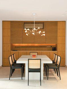Apartamento carioca de 185 m²/ Ivan Rezende / Painel de carvalho-americano (CAP Marcenaria) esconde louça, copos, talheres e ar-condicionado. Ótimo para sala de jantar.