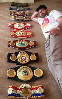 Controversial boxer Tyson Fury poses with all his belts one last time before relinquishing them