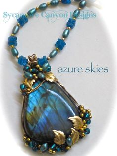 """azure skies""... I have wrapped this striking Labradorite in square antique brass and 14kt gold filled wire and I am framing it with brass leaves, teal colored rice Freshwater Pearls, glass beads and brass beads. It is on an 17"" strand of Apatite, rice Pearls and brass beads."