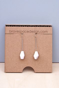 The Iceberg Earrings combines stark white Corian and antiqued silver chain to create a style all of its own. These hand-made gems are salvaged in the making of furniture and feature versatile tones and texture. Variations in material and shape should be expected from what is shown in the images as every piece is made by hand.  $40