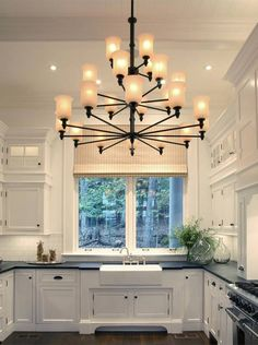 The kitchen, with views of the woods, has 12-foot-high ceilings and white-painted cabinets with soapstone countertops. (Andreas Trauttmansdorff)