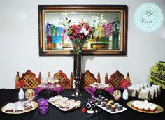 Mesa de Postres con tema de día de muertos, bolsitas de papel con churritos, galletas decoradas en forma de calavera, calaveras de chocolate, brownies, mini tartas, pay de limón en copitas y panquecitos de naranja.
