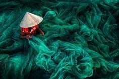 Bức ảnh sống động miêu tả người phụ nữ đội nón truyền thống đang đan lưới đánh cá theo phương pháp thủ công tại một ngôi làng chài ở tỉnh Phan Rang,Việt Nam. Việc đan lưới đánh cá thủ công là một trong những hoạt động tiêu biểu cho phụ nữ Việt Nam trong khi đàn ông ra khơi