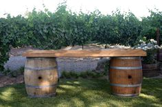 """March  Wine Barrel Bar - This bar consists of 2 wine barrels and a rustic wooden top that is 32"""" deep and 90"""" wide. With the depth of this bar you have the ability to not only use it for a bar, but also for a wonderful display for your cake, lemonade stand, food, or so much more. This bar is a perfect addition to a rustic styled event. The Wine Barrel Bar is priced at $100.00"""