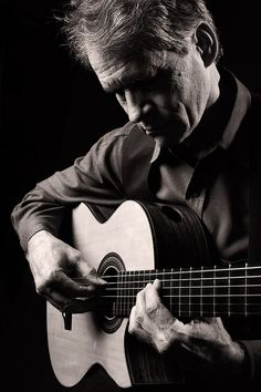Dramatic musician portrait, acoustic guitar musician, low key black and white portrait