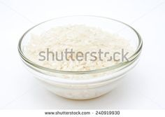 Grains of organic rice in a glass bowl selective sharp area isolated on white background.